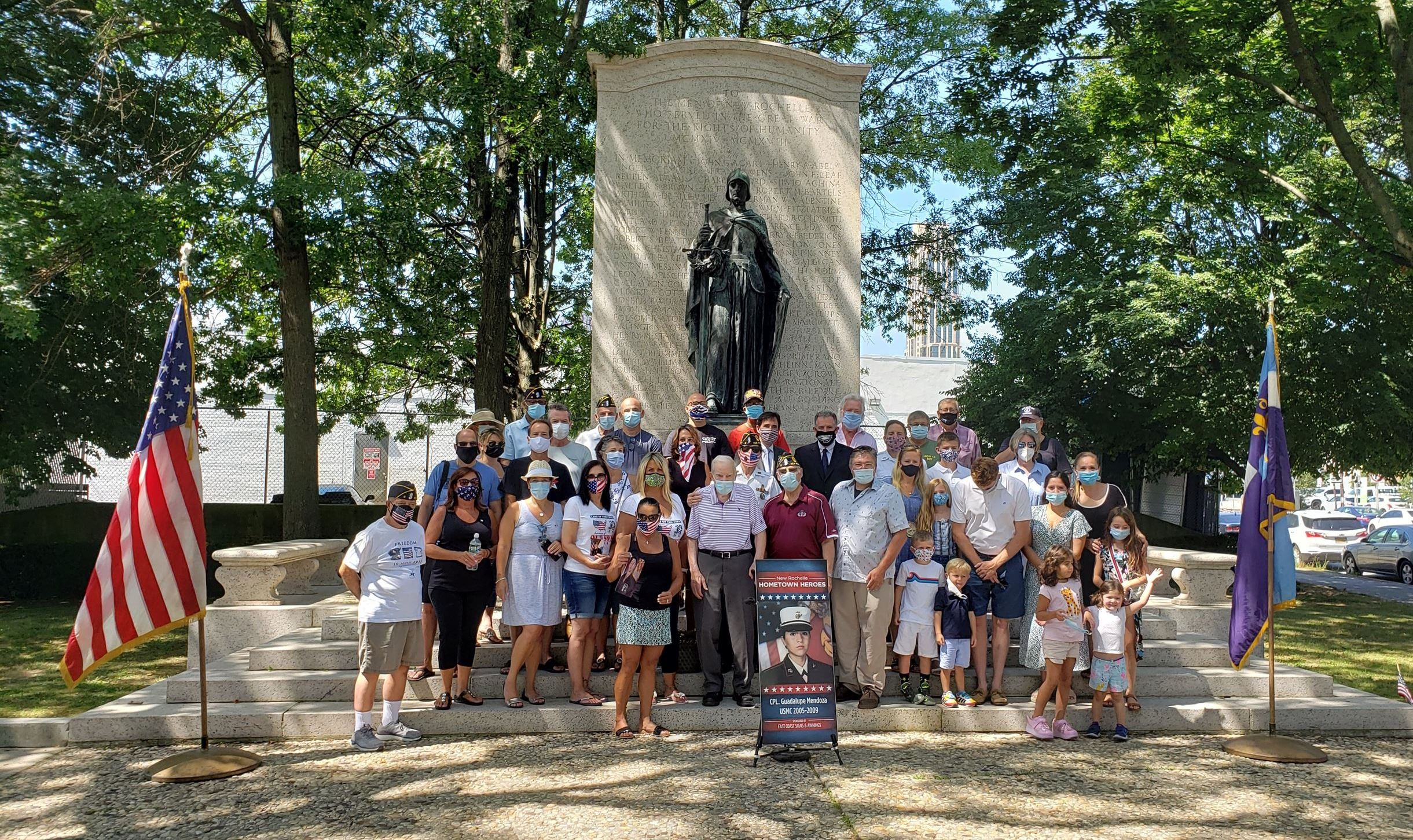 Group shot with poster of veteran banner in front of WW1 statue at Faneuil Park